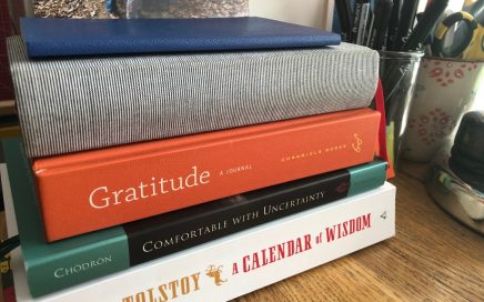 Five books piled up: Leo Tolestoy's Calendar of Wisdom, Pema Chodron's Comfortable with Uncertainty, a gratitude journal, a 5-year journal, and a small commonplace notebook